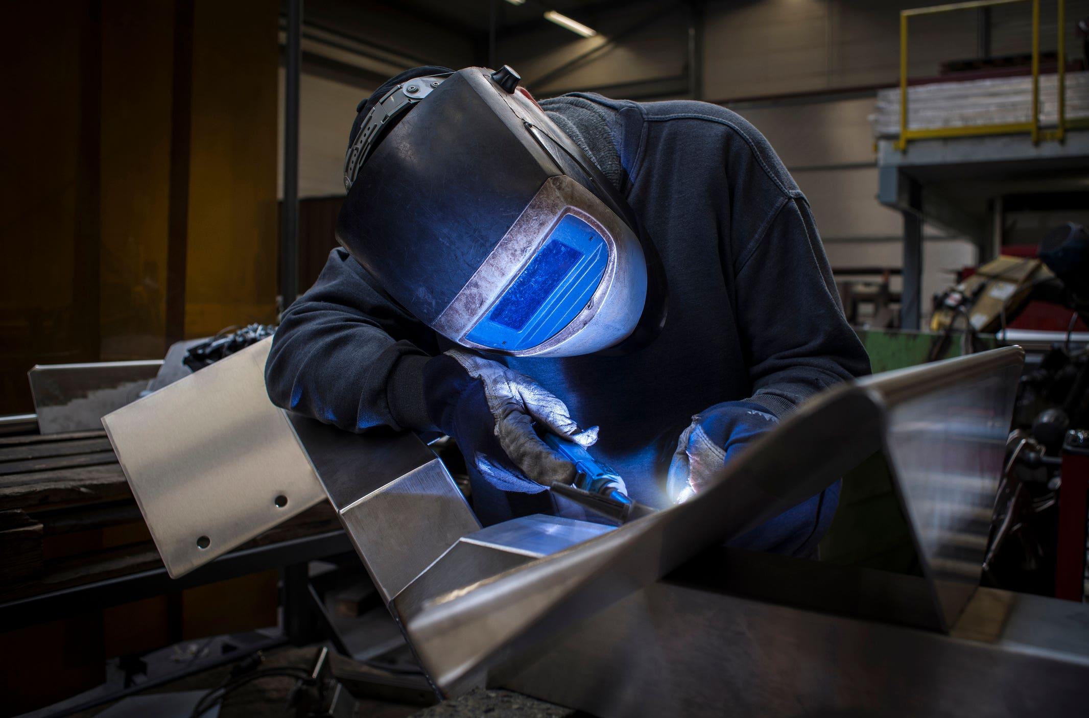 Welder in shop working with metal